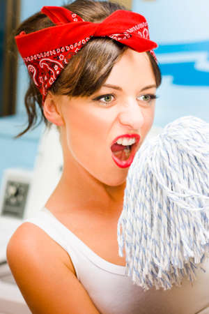 enjoyable: Pretty Woman Rocks Out To House Work Chores While Singing Into The Top Of A Mop In A Fun Playful And Crazy Concept Of Enjoyable Home Work Stock Photo