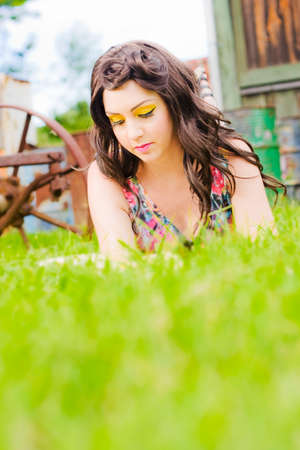 captivated: Grass Eye Level View Of A Girl Lying On A Grass Lawn Perusing And Reading A Book Of Poetry In A Beautiful Summer Portrait