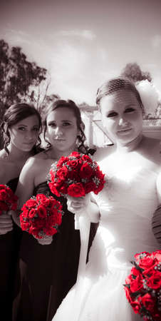 white colour: Bride With Two Bridesmaids Holding Multiple Bouquets Of Red Roses With Elegant And Graceful Expressions, Black And White With Bright Red Roses