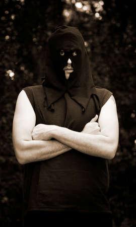 ahorcado: Un Negro encapuchado verdugo mata el tiempo en un bosque que cuelga alrededor mientras esperaba su próxima víctima