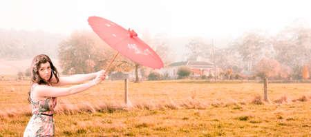 bygone: Vintage Rural Landscape Portrait Of A Caucasian Woman Holding A Parasol Or Umbrella On A Autumn Farm Field In A Reminiscent Nostalgic And Bygone Portrait