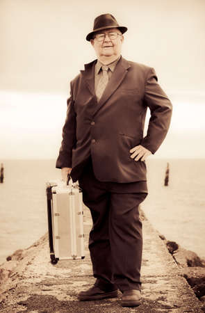 olden: Nostalgic Photograph With Slight Solarisation Of A Vintage Traveling Business Man Wearing Suit And Tie With Metal Suitcase While On A Travel Tour Of Olden Days