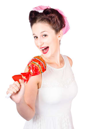pop star: Isolated portrait of a funny pin-up sing star talking into large lollypop microphone. Pop star karaoke Stock Photo