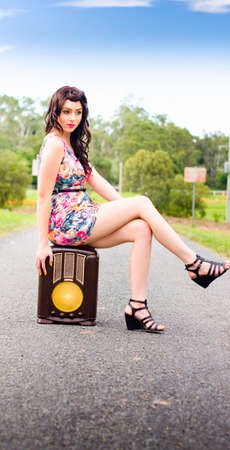 poised: An Attractive Brunette Female Sitting On An Antique Radio With Poised Expression Against Trees And Blue Sky Background