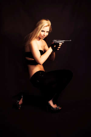 clandestine: Sexy blonde lurking in the shadows with a handgun cocked and ready in a private investigator or assassin concept