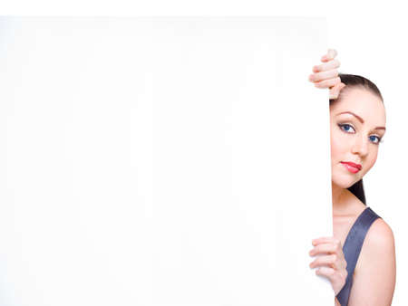 bargains: Studio Image Of A Happy Business Woman Hiding Behind A Huge Banner Add In A Commercial Display Of Bargains And Cheap Discounts, Room For Text On White Stock Photo