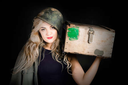 bombshell: Dark retro army picture of an attractive young pinup soldier girl in cadet hat standing with ammunition supply box. Blond bombshell Stock Photo