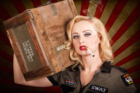 allies: Grunge WWII military pinup girl with 1940s blond hair style and makeup carrying weapons ammunition box on shoulder in vintage army fashion. Western allies war beauty