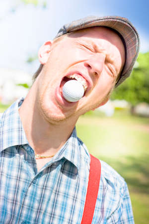 daft: Humorous Head And Shoulders Portrait Of A Young Mans Reaction On A Golf Course Immediately After Catching A Flying Golf Ball In His Open Mouth