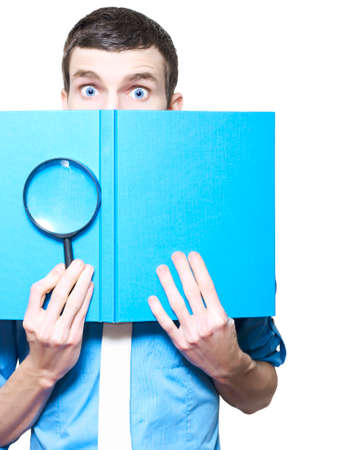 embarassed: Isolated Male Business Person Holding Magnifying Glass And Textbook In A Book Review Concept On White Background