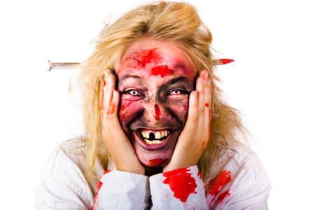 crazed: Portrait of crazy blood covered female zombie smiling with nail piercing through head, white background