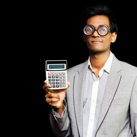 nerdy: Nerdy asian accountant or maths genius wearing glasses and suit holding calculator isolated on dark background Stock Photo