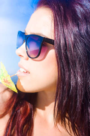 nibbling: Partying Person Wearing Sunglasses And Nibbling On The End Of A Cocktail Or Drink Parasol At An Outdoor Party While On A Fun And Entertaining Pleasure Cruise