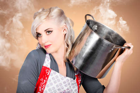 homemakers: Retro women and homemakers. Beautiful young blond pin up woman cooking food in a steamy kitchen