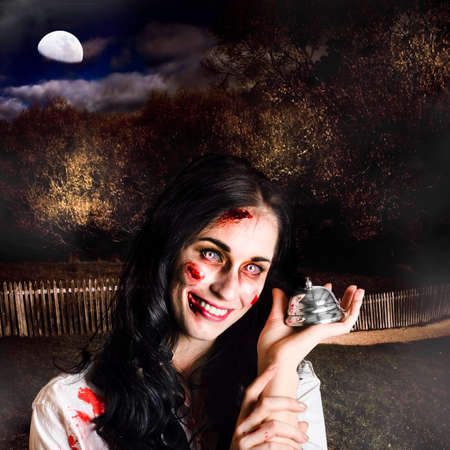cadaver: Creepy deceased zombie woman holding silver service bell in a spooky graveyard location in a depiction of death services Stock Photo