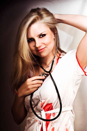 own blood: Beautiful smiling young blonde nurse holds a stethoscope to her heart in a concept of being love struck.