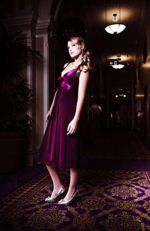 стиль жизни: Красивая блондинка женщина позирует в затемненном холле отеля в шикарном фиолетовом вечерний наряд ждет своего дня вечернего свидания Фото со стока