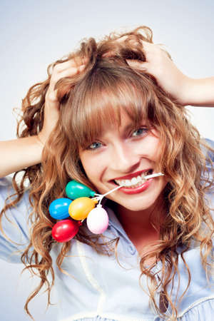 tousled: Excited woman enjoying her birthday party as she laughingly grips a colourful bunch of mini toy party balloons between her teeth