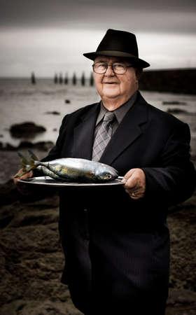 fischerei: Serious Man Bei Dunkelheit am Strand h�lt einen Teller mit Fisch mit einem fragenden Ausdruck in einer Fischerei �ber den Verbrauch nat�rlicher Ressourcen Lizenzfreie Bilder
