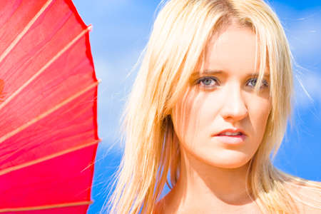 health fair: Young Blonde Woman With Alluring Expression Standing Against A Blue Sky With Pink Sun Umbrella As If She Is Living Within A Dream