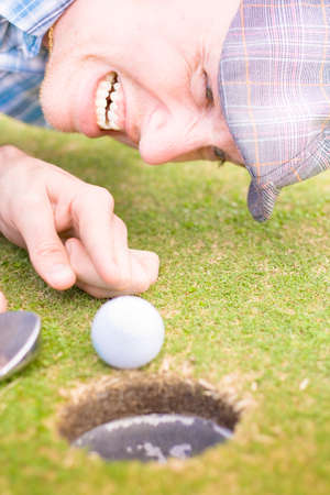 dissapointed: Unsuccessful Golfer Points In A Expression Of Frustration And Disappointment At His Golf Ball Just Shy Of The Hole In A Unlucky In Sport Conceptual