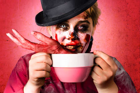 fiend: Creepy female zombie holding big soup cup containing severed and mutilated hand. Halloween cooking concept