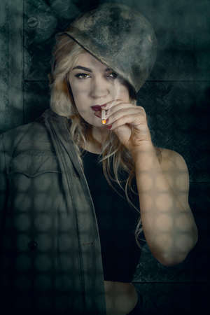 sombre: Dark melancholy war portrait from 1940 of a sombre female pinup soldier smoking cigarette in a dreary lit foxhole during a dawn combat op. Night watch Stock Photo
