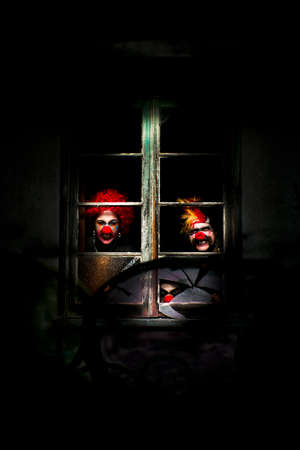 broken house: Three Evil Looking Clowns Peering Out The Window Of A Shadowy Building Stock Photo