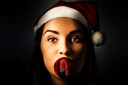 christmas funny: Funny dark xmas concept on the face of a surprised silly season santa girl getting crazy with christmas decoration. Little tree helper