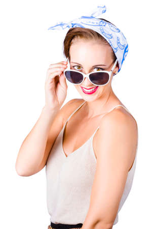 peering: Attractive smiling model posing in  chemise and head scarf and peering over her sun glasses Stock Photo