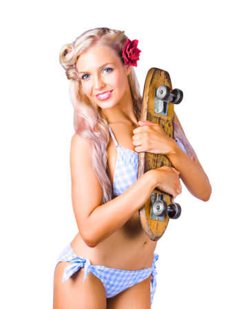 50s: Attractive blond 50s woman in bikini holding skateboard on white background