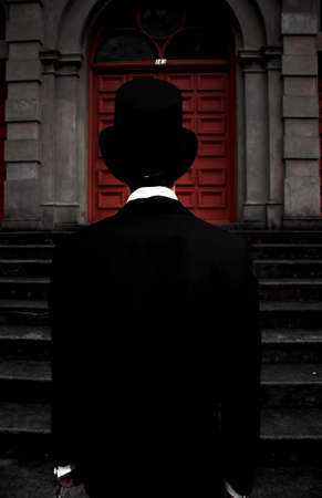 stair well: Dark Man In Black Suit And Top Hat Stands At The Bottom Of The Stairwell Of Darkness Stock Photo