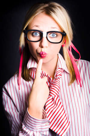 puckered lips: Young attractive blonde girl wearing dorky eyeglasses puts index finger to puckered lips in a work secrets concept Stock Photo