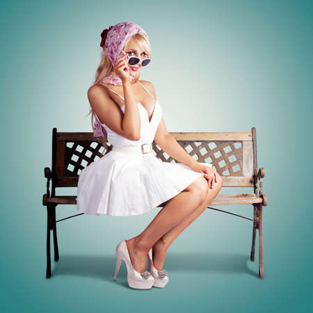 headscarf: Classic Fashion Portrait Of A American Blond Beauty Sitting On A Park Bench Wearing Fashionable Headscarf, Sunglasses And White Retro Dress. On Green Background Stock Photo