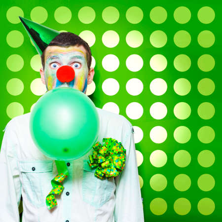 clowning: Excited Male Clown With Colourful Face Paint Blowing Up A Green Balloon While Having Fun Celebrating Kids Birthday Parties