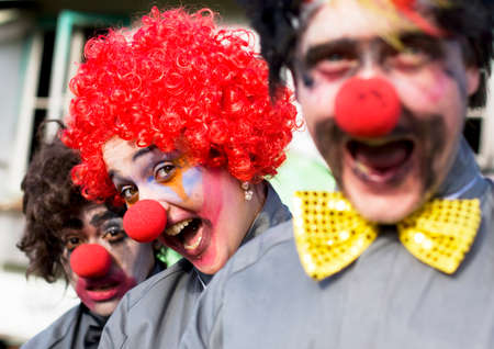 clowning: Focus On The Faces Of 3 Crazy Circus Clowns At An Outdoor Birthday Gig Clowning Around In A Funny And Comical Show Of Entertainment