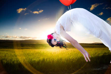 high spirited: Free Spirited Woman Drifts With Two Balloons High In A Cloudy Sky Above A Beautiful Landscape Farmyard Field In An Image Representing Growth And Freedom Stock Photo