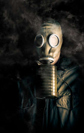 wafting: Eerie atmospheric portrait of a soldier in a gas mask and canister with noxious fumes swirling about his head in the darkness in a biohazard, death and destruction concept