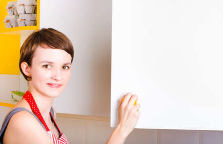 pantry: Cute young brunette woman with short hair looking for food ingredients in copyspace pantry cupboard in a food supplies conceptual