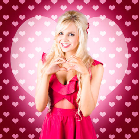 truelove: Pretty blonde girlfriend gesturing heartfelt feeling of romance with hands. Pink hearts background