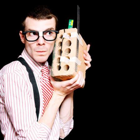 estereotipo: Hombre inteligente Nerd Inventor Holding A State Of The Art House ladrillo transformado en un teléfono móvil en un concepto de innovación de la novedad
