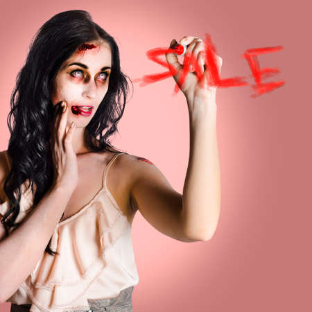 reanimated: Scary business woman writing sale in blood on a shop glass window in a depiction of Halloween sales