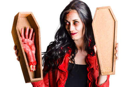 severed: Beautiful vampire girl smiling and showing a bloody severed hand in a small coffin in a good mourning welcome concept