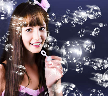 pert: Cute smiling female blowing lots of soap bubbles during a birthday party celebration