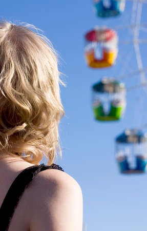 wheel spin: Back Of A Curly Haired Blond Woman As She Watches A Colourful Ferris Wheel Spin At A Fun Fair