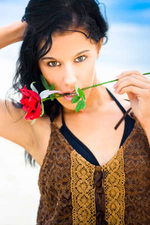 intriguing: Attractive Young Woman With Beautiful Black Hair And Mystical Expression With A Single Red Rose Against A Blue Sky Background Stock Photo