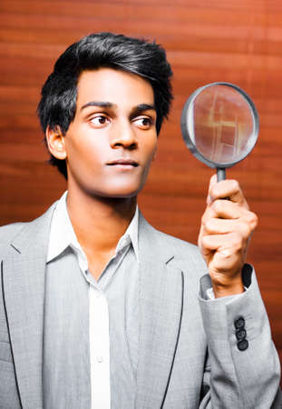 clues: Conceptual image of a young male business auditor holding up a large magnifying glass as he delves for the truth in a financial audit to verify statements and returns of a corporate business