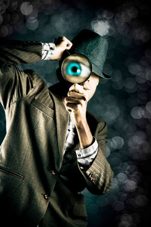 undercover: Private Eye Spying And Searching Through A Magnifying Glass At Night During A Stealth Undercover Operation To Reveal And Find The Hidden Truth Stock Photo