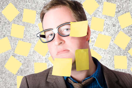 yellow tacks: Stressed businessman wearing empty memo papers on body and on concrete office wall behind while undertaking huge work assignment Stock Photo