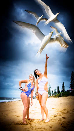 one female: Flock Of Flying And Airborne Birds Migrating In A Cloudy Blue Sky Past Two Female Swimmers With One Pointing Up In A Nature And Environment Concept Stock Photo